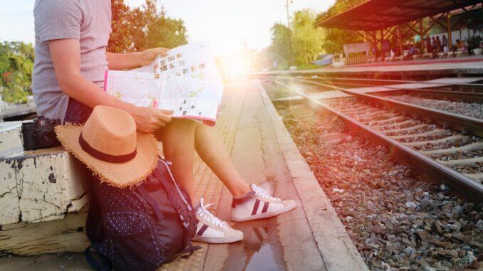 Person med taske venter på tog med kort