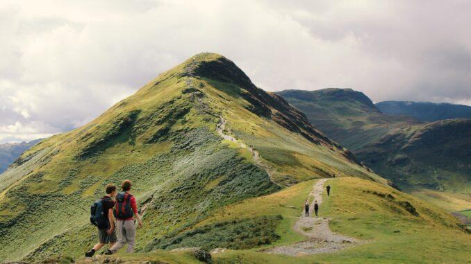 Personer går på toppen af bjergkæde