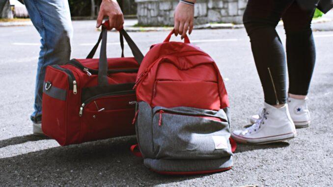 To mennesker stiller røde tasker på jorden