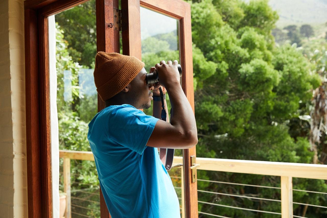Person kigger ud af vindue med sin kikkert